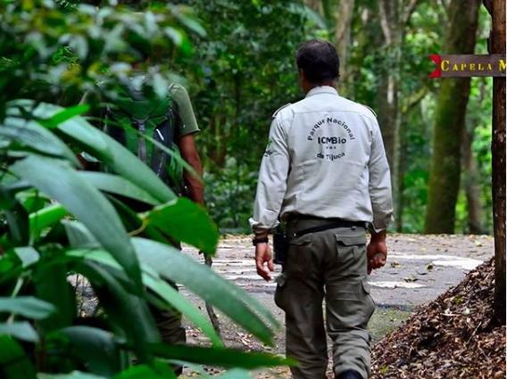 Imagem mostra funcionário do Parque Nacional da Tijuca caminhando dentro do parque acompanhando de um monitor de trilhas do parque