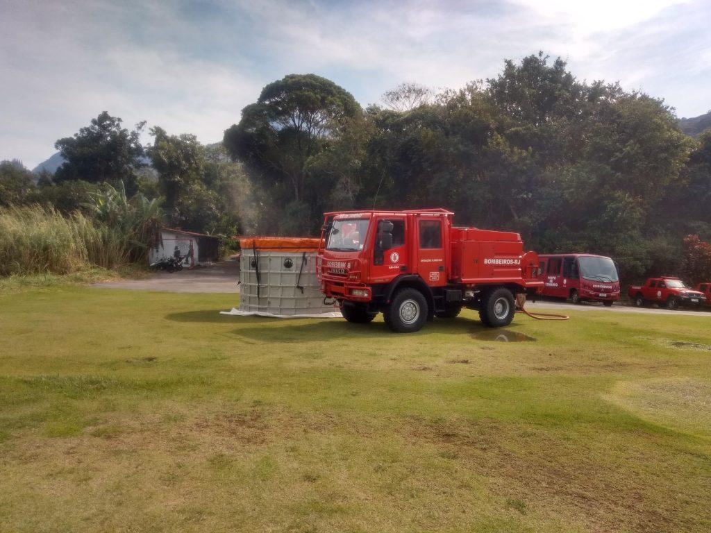 Caminhão dos bombeiros parado ao lado de um tanque cheio de água